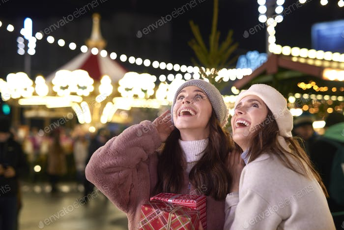Women outdoors with Christmas gift looking away