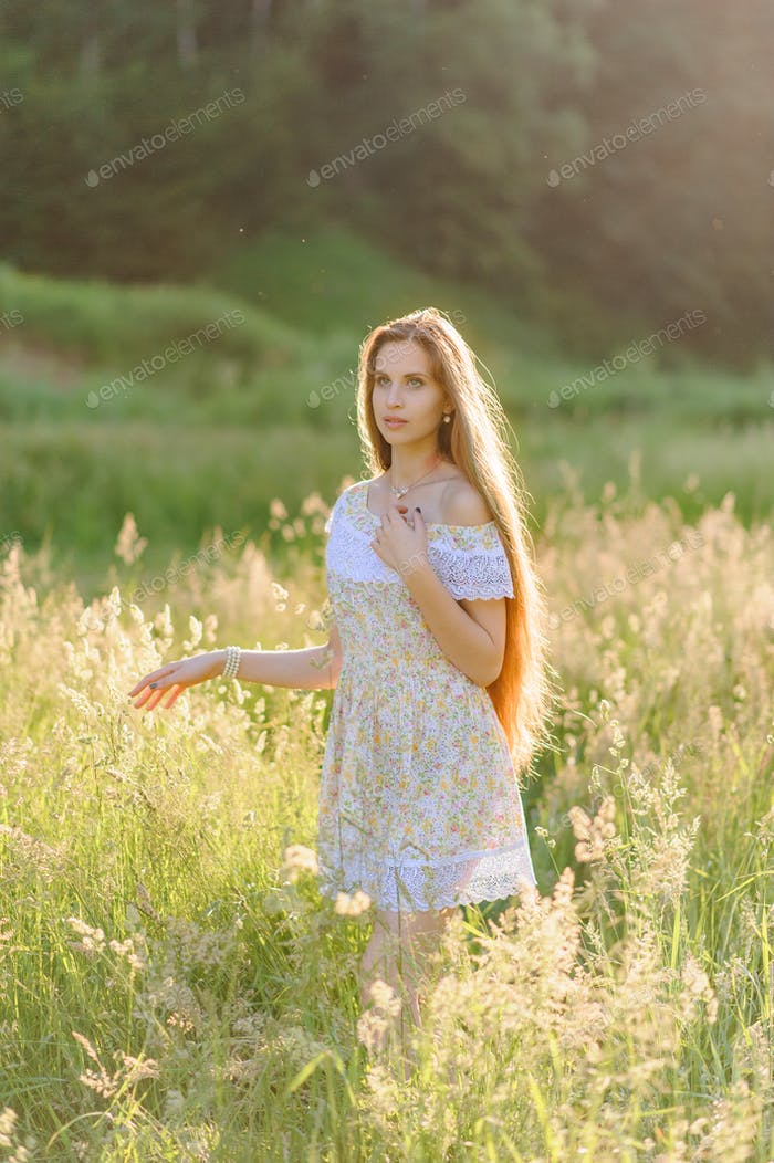 Portrait of a young beautiful girl in a sundress. Summer photo session in the park at sunset.