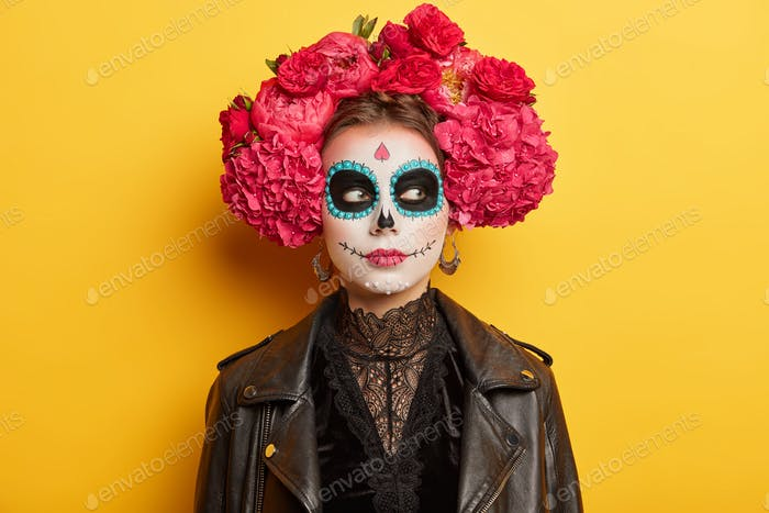 Portrait of thoughtful woman with painted face has sugar skull makeup wears flower wreath and leathe