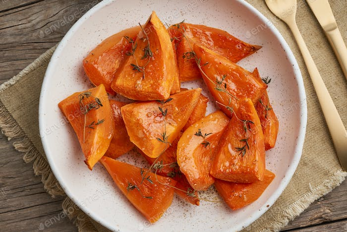 roasted pumpkin, pieces in plate with honey and seasonings