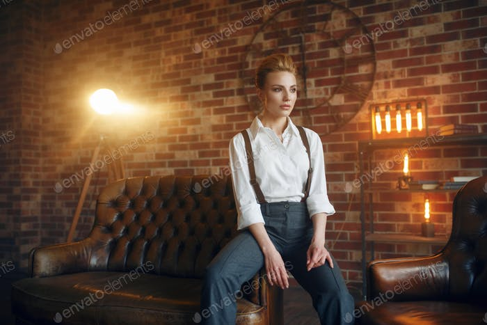 Business woman in strict clothes on leather couch