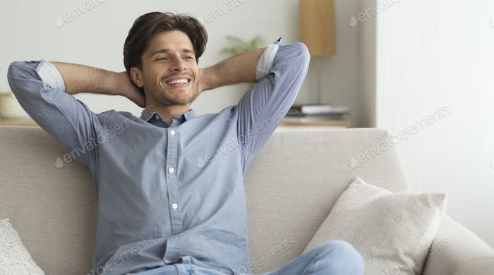 Happy Guy Relaxing Sitting On Sofa At Home