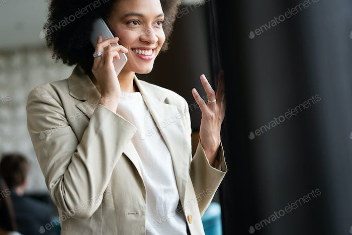 Beautiful successful black businesswoman with smartphone in office