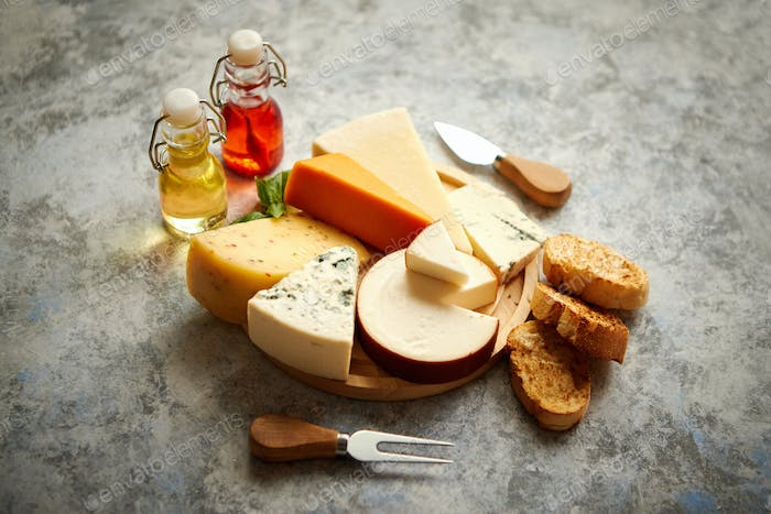Various types of cheese served on rustic wooden board