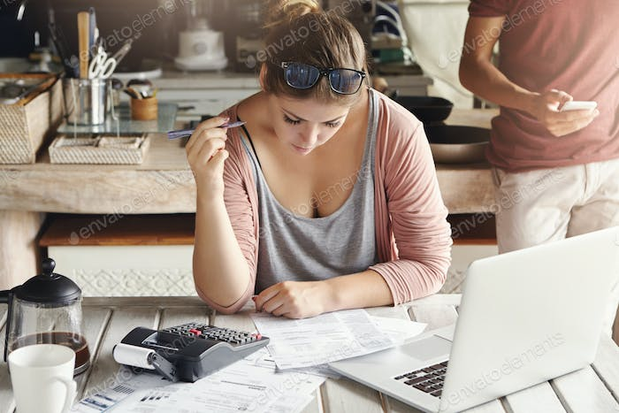 Family budget and financial problems. Concentrated worried woman doing paperwork at home, calculatin