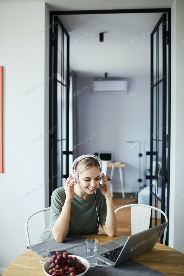 Happy young female in headphones interacting through video-chat