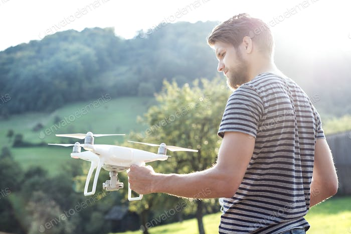 Thumbnail for Young hipster man holding drone. Sunny green nature.