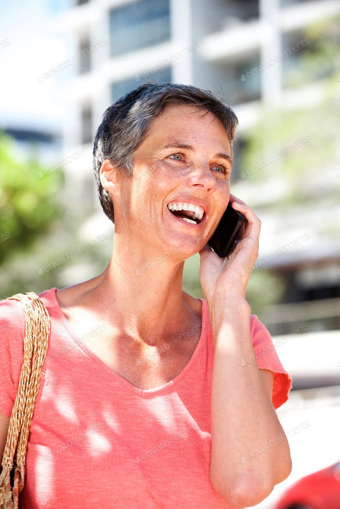 happy mature woman talking on mobile phone outdoors
