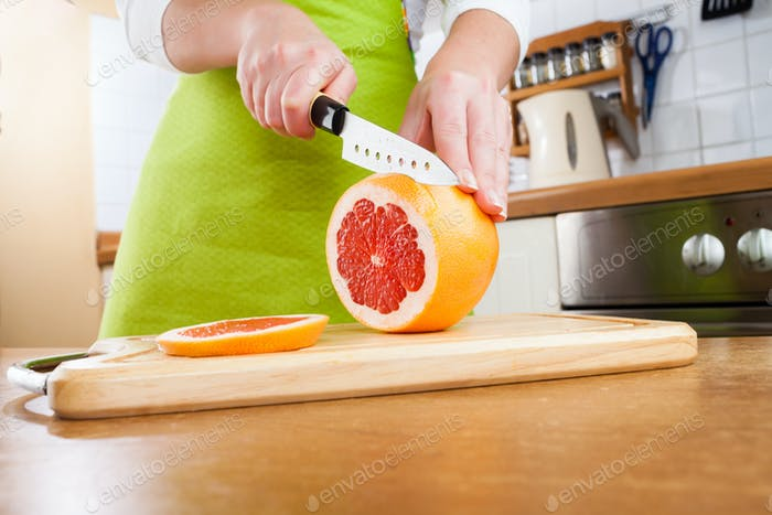 Woman's hands cutting grapefruit