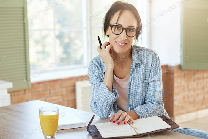 Creative female worker being at home, writes notes and plans her schedule, looks into camera. Woman