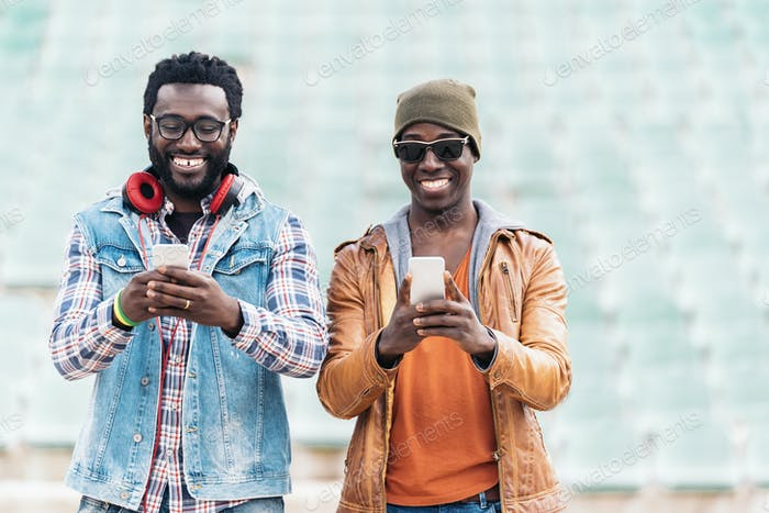 Two black race friends having fun with mobile.