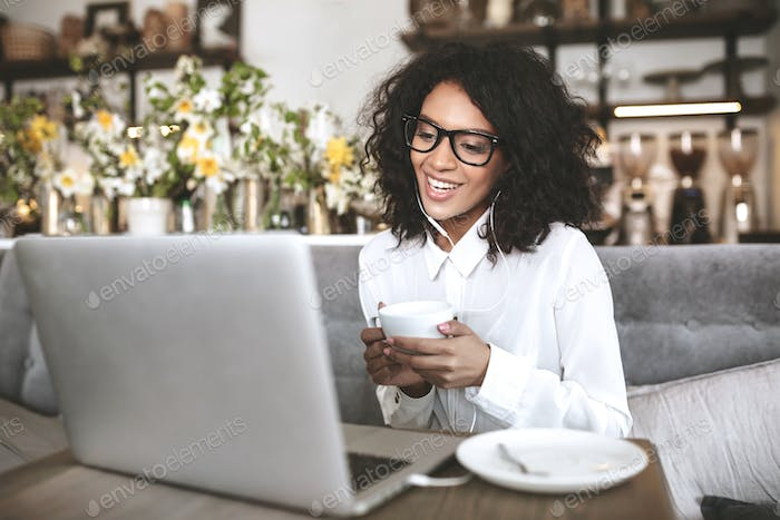 Young African American girl in glasses sitting in restaurant with laptop and cup of coffee in hands