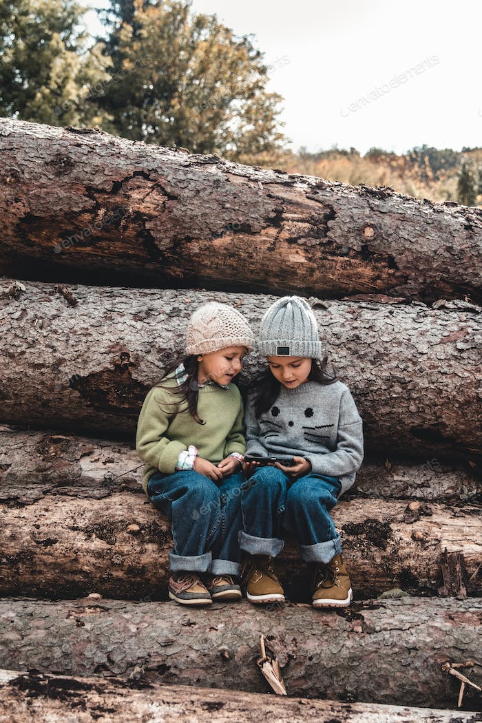 Children in the background of logs play with a smartphone. Watch the video and have fun. Friendship