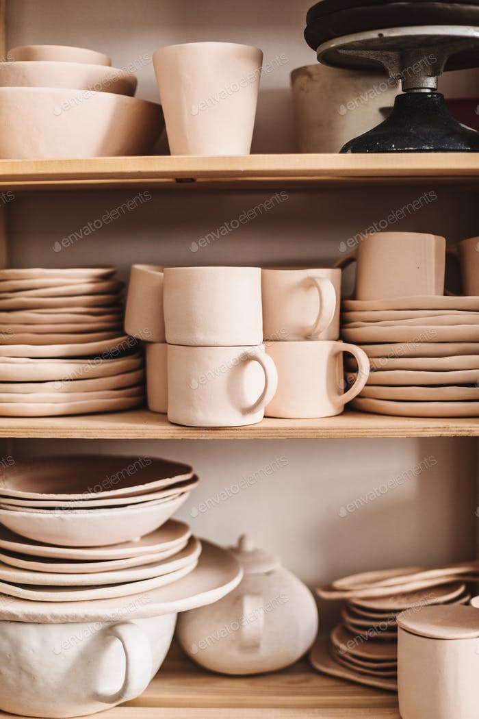 Close up handmade clay dishes on wooden shelves at pottery studio