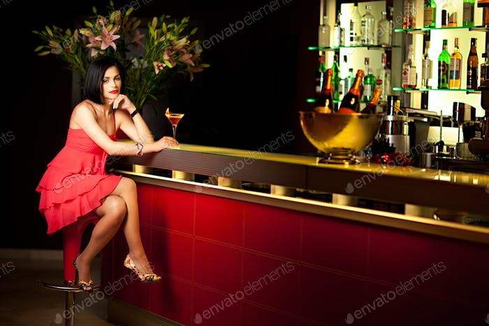 lady in red sitting at the bar