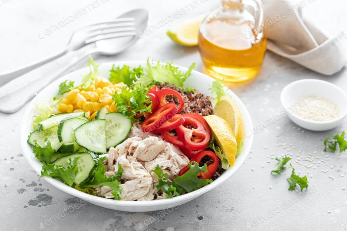 Chicken meat lunch bowl with fresh salad leaves, corn, cucumber, sweet pepper and quinoa