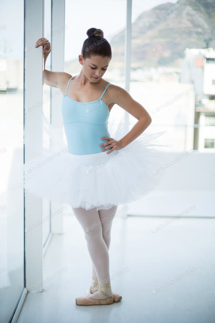 Thoughtful ballerina standing near window