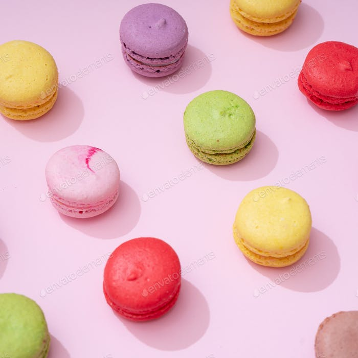 Pastel pink table top with colorful macarons pattern. Minimal sweet food concept. Cookie concept.