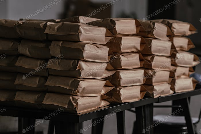Pile of coffee craft bags packages on black table