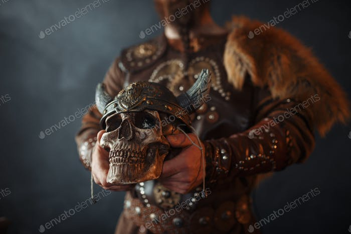 Viking holds human skull in helmet