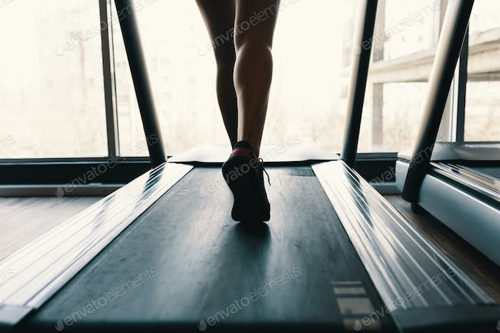 Early morning sport, female legs running on the gym treadmill early morning
