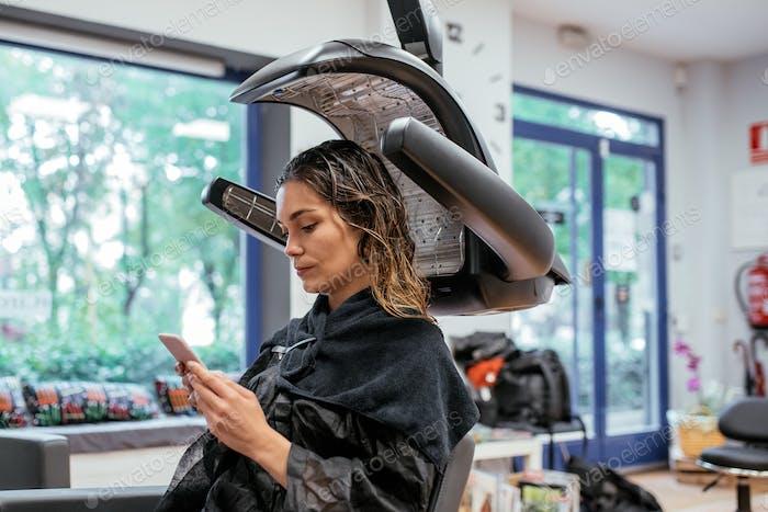 Mujer en una peluquería profesional secador de pelo infrarrojo