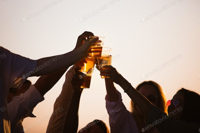 Group of friends clinking beer glasses during picnic at the beach. Lifestyle, friendship, having fun