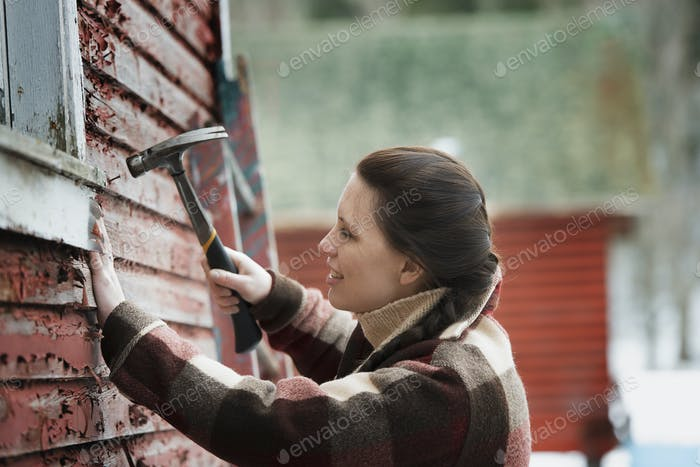 A woman with a hammer repairing the shingles on a barn.
