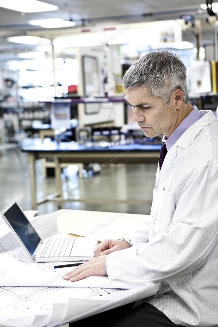 A male caucasian technician in white coat using a laptop computer