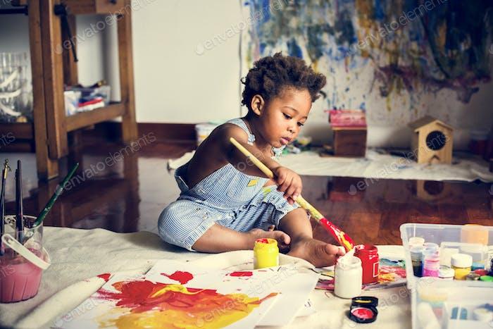 Black kid enjoying his painting