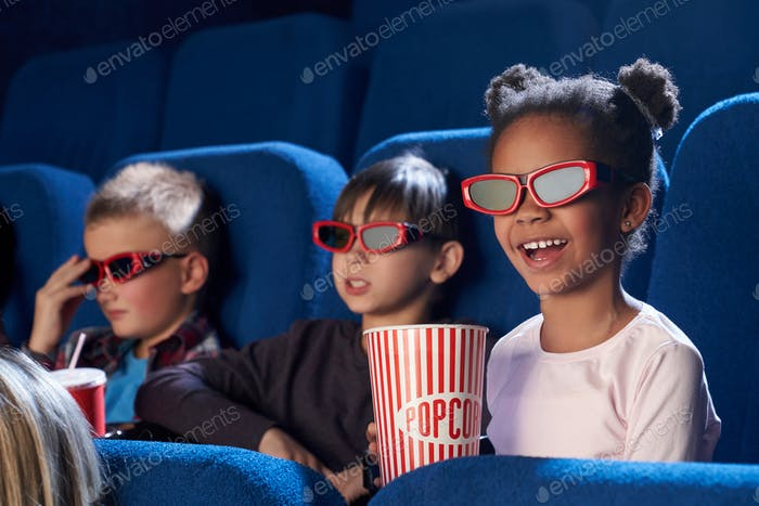 Happy child in 3d glasses watching comical movie in cinema