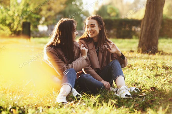 Young smiling brunette twin girls sitting on grass with legs crossed