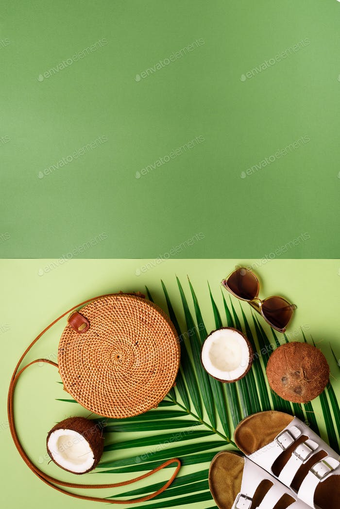 Stylish rattan bag, coconut, birkenstocks, palm branches, sunglasses on olive green background