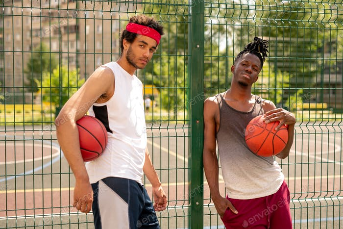 Two active guys in sportswear standing by fence surrounding basketball court