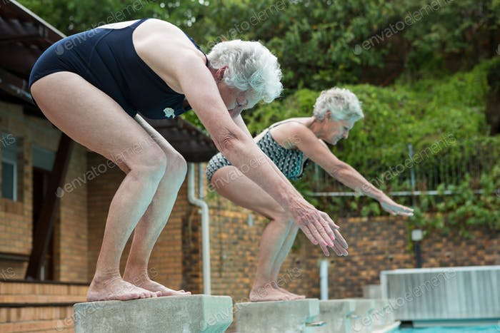Two senior women preparing to dive in pool