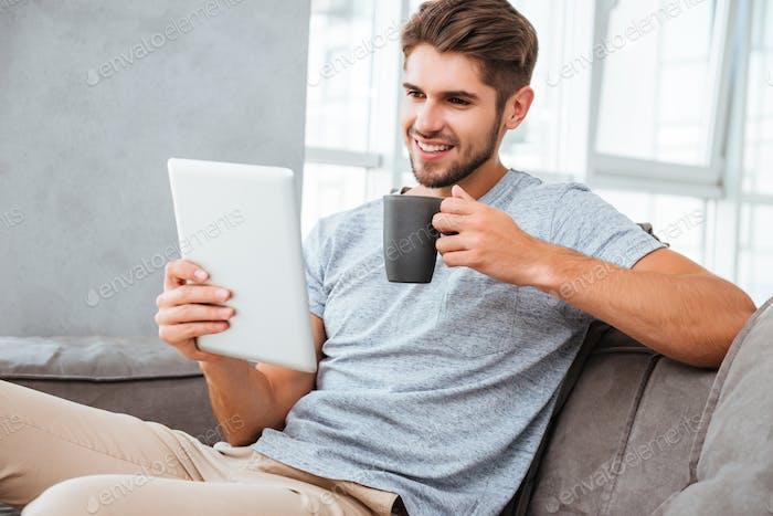 Fröhliche Mannkommunikation per Tablette beim Trinken eines Kaffees
