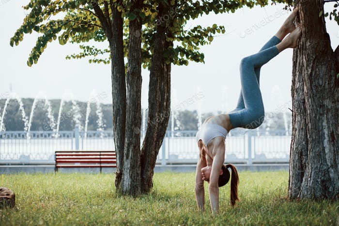 Using tree to keep balance. Young woman with slim type of body does exercises in the park
