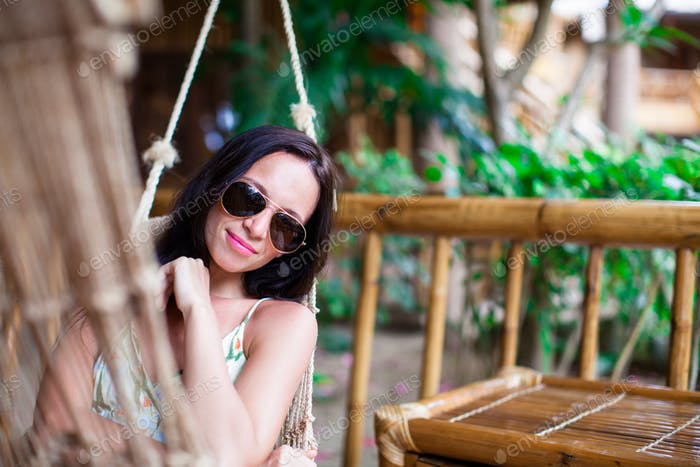 Beautiful brunette woman relaxing in hammock at exotic luxury hotel