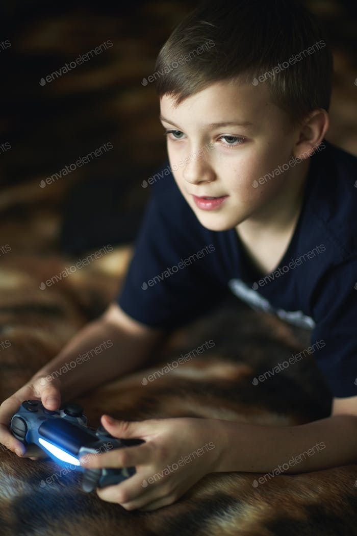 A teenager is sitting on the sofa and playing