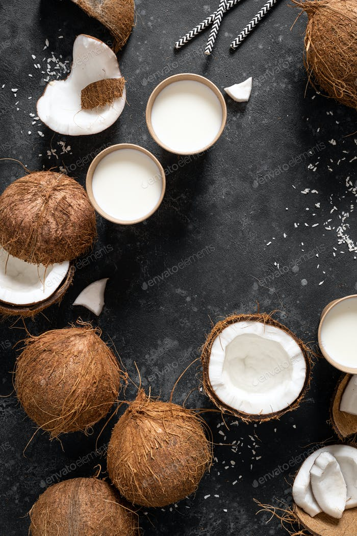 Coconut milk, whole and cracked coconuts on black background, top view