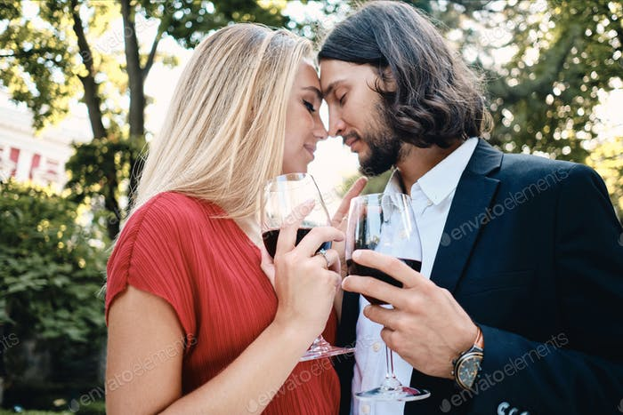 Sensual couple with glasses of red wine dreamily celebrating engagement in restaurant outdoor