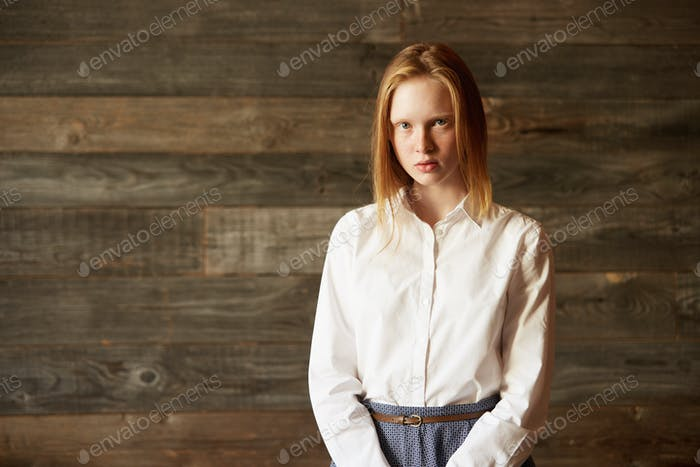 Portrait of a beautiful Caucasian woman looking seriously at camera. Blond girl well-dressed in whit