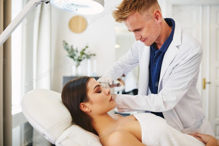 Young doctor performing botox injections on a young female client