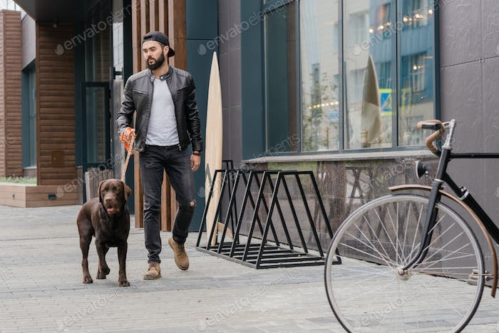 Bearded young man in jeans and leather jacket chilling with purebred dog