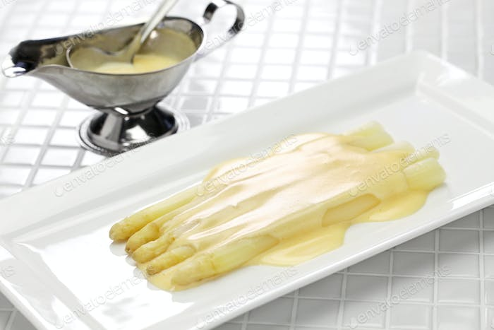 Hollandaise sauce is poured over white Asparagus.