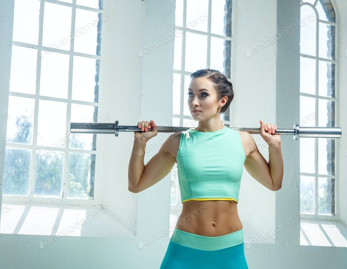 An athletic, sporty female dressed in an azure sportswear holds barbell.