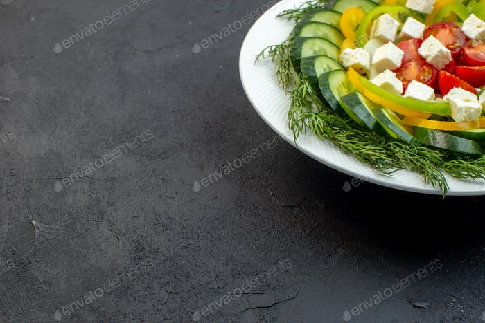 front view vegetable salad consists of sliced cucumbers tomatoes pepper and cheese on dark