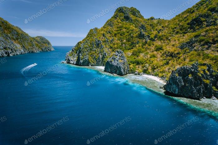 Kalkstein-Karstküste der Insel Matinloc mit touristischen Booten in Meeresstraße. El Nido (Palawan  )
