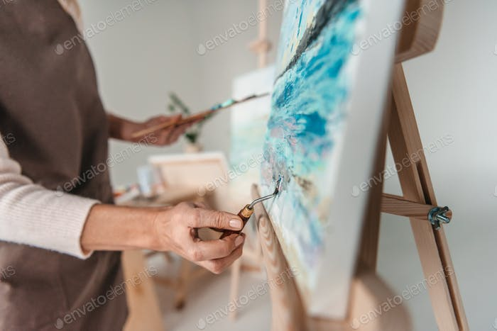 selective focus of artist with art tools drawing on easel