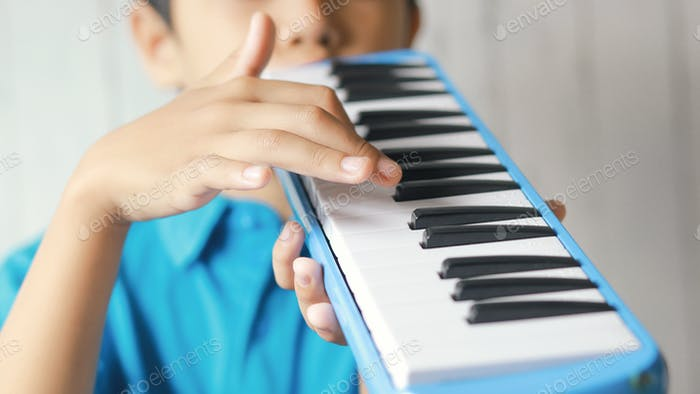 Boy playing blue melodeon or pianica